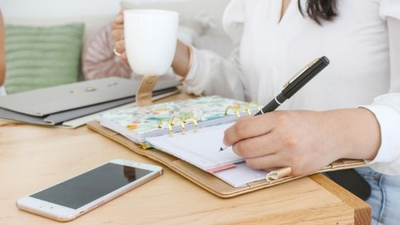 photo of a woman drinking coffee and writing in her journal