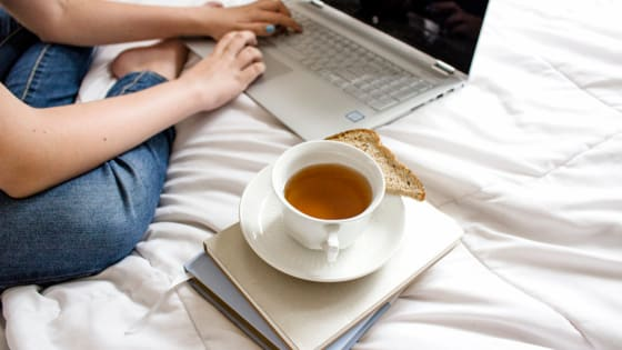 a woman sitting on the bed working on her computer with a cup of tea