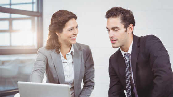 An image of a woman attorney explaining to her male client about legal issues in front of a laptop computer.