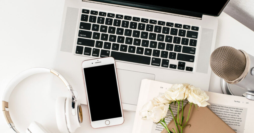 An image of laptop, phone, microphone and flowers all acting as the featured image for my best blogging online courses post