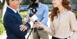 An image of a journalist woman interviewing a business owner